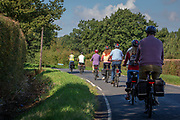 A line of cyclists on electric bikes travel along a Cradducks Lane country road in Staplehurst, Kent, England, UK.  (photo by Andrew Aitchison / In pictures via Getty Images)