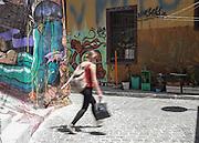 A woman walks through an alley lined with street art in Cerro Alegre, Valparaiso.