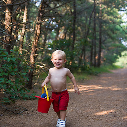 A young boy (age2) heads to the beach at the Cape Cod National Seashore in Truro, Massachusetts.  Path from North of Highland Campground.