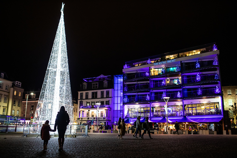 Mum and child looking at the Christmas tree and lights in the Weighbridge Square at night, with festive lights glowing from the Royal Yacht Hotel, Jersey