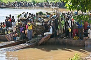 A ferry carries a full load of farmers and traders across the Mpoko river in Kattin, just outside of Bangui. Most people in Central Africa are subsistence farmers and traders, and live off of a dollar a day. They farm manioc, peanuts, maize, bananas, and harvest tress for firewood.