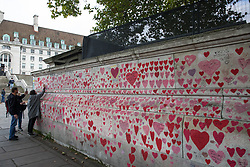 A member of the public writes a dedication on the National Covid Memorial Wall on the South Bank of the River Thames on 15th October 2021 in London, United Kingdom. The National Covid Memorial Wall is a public mural comprising thousands of red and pink hearts painted by volunteers in order to commemorate the victims of the COVID-19 pandemic in the United Kingdom.