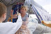 Boy age 8 purchasing bread necklaces (obwarzanek) at sidewalk market (rynek).  Tomaszow Mazowiecki Central Poland