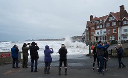 © Licensed to London News Pictures. <br /> 21/03/2015. <br /> <br /> Sandsend, North Yorkshire.<br /> <br /> People gather to take photographs as waves crash against the sea wall at Sandsend in North Yorkshire. The exceptionally high Spring tides were created by the moon's 18-year cycle.<br /> <br /> Photo credit : Ian Forsyth/LNP