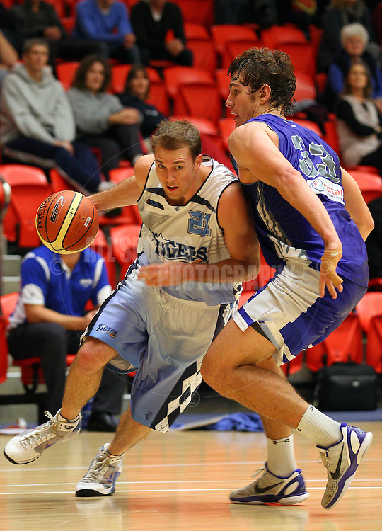 PERTH, AUSTRALIA - JULY 16: Troy Thomson of the Tigers drives past Ben Purser of the Hawks during the week 18 SBL game between the Perry Lakes Hawks and the Willetton TIgers at The State Basketball Center on July 16, 2011 in Perth, Australia.  (Photo by Paul Kane/Allsports Photography)