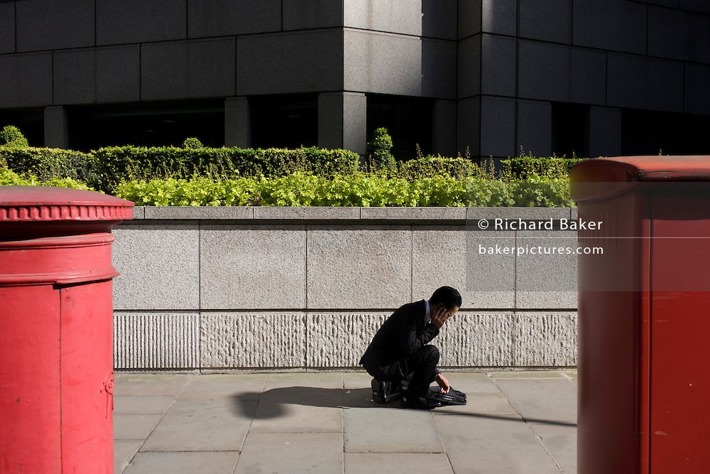 A businessman crouches to check messages by an urban garden of bushes and shrubs.