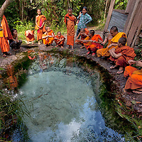 Monks sitting around a pool in Phnom Kulen which sabulous ground is permanently circulated due to an underground spring.