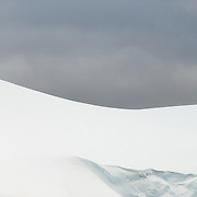 "Snow and ice covering mountain ridges creates shapes against the gray overcast skies behind in the Lemaire Channel on the western side of the Antarctic Peninsula. The Lemaire Channel is sometimes referred to as ""Kodak Gap"" in a nod to its famously scenic views."