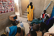 A soccer match, and later a TV crime show from Los Angeles, on a black and white car-battery-powered television holds a large, rapt audience of village men outside the barber's area in Kouakourou, Mali. The car battery is recharged by a photovoltaic solar cell on the roof of the barbershop. From coverage of revisit to Material World Project family in Mali, 2001. Africa.