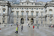 As temperatures rise in Britain children play in the fountains at Somerset House, central London.