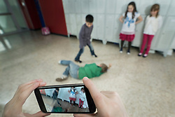 Person's hand filming two schoolboys fighting in school corridor with mobile phone, Bavaria, Germany