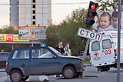 Moscow, Russia 13/05/2007..Passersby use cellphones to photograph a drunken driver's car after he crashed into a stop sign at at a road junction. The man was uninjured but was so drunk he could not walk without assistance.