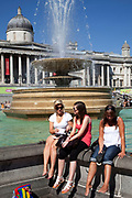 Tourists and locals relax in the Summer sun at Trafalgar Square, central London. People come to cool off by the fountains, relax in deck chairs whilst visiting the National Gallery and other attractions.