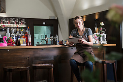 Restaurant owner using tablet while sitting by bar counter