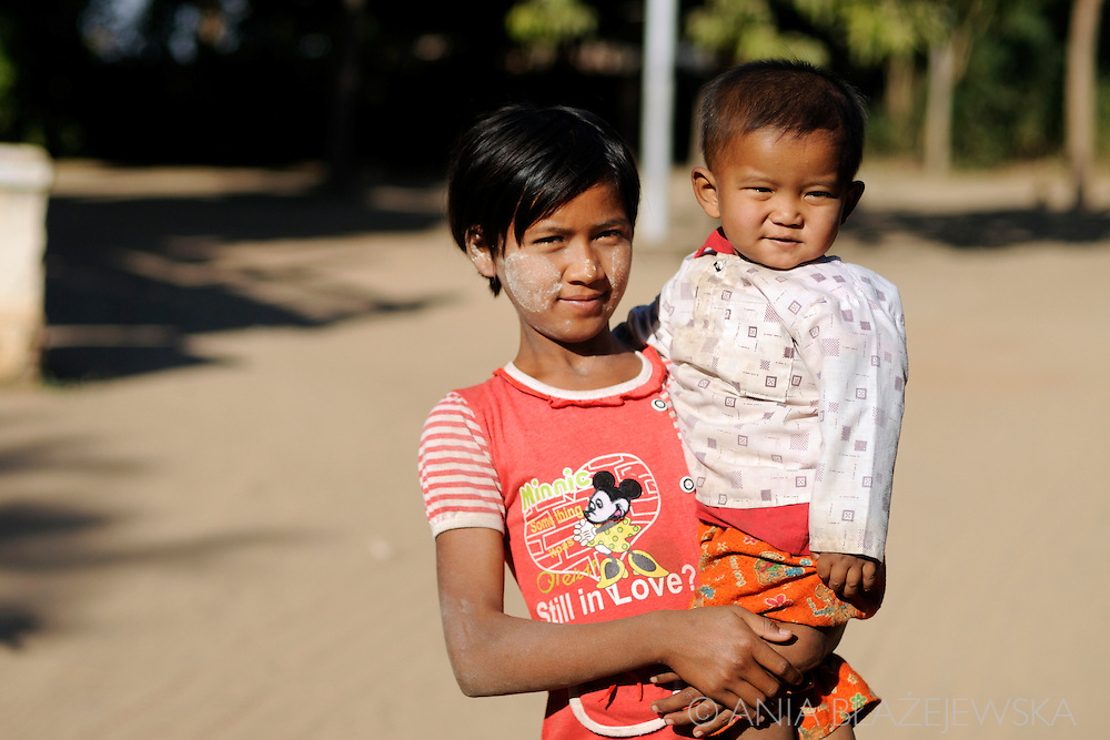 Burma/Myanmar, Bagan. Young girl from a small village near Bagan is looking after her little brother.