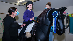 East Lothian, Scotland, UK, NHS Lothian & Muirfield Riding Therapy celebrates 10 years of Hippotherapy:  Physiotherapist Heather Falconer pioneered The Children's Therapeutic Riding Service providing therapeutic riding free of charge to children, young people and adults with disabilities. The service was the first in Scotland for children with mobility, balance, muscle tone and coordination problems. Oreo, a mechanical horse, allows youngsters to have fun physiotherapy. Kyle Clark, aged 8 years, rides Oreo.<br /> Sally Anderson | EdinburghElitemedia.co.uk