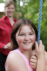 Young girl developing a trusting and close relationship with her mentor while having fun on a tree swing; part of the Independent Visitors Scheme,