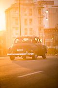 Vintage cars on Malecon city street at sunset, Havana, Cuba
