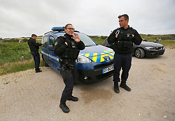30 June 2020. South of Calais, France.<br /> Smugglers' Paradise. 'Gendarmes National' - National police wait for me at my car early in the morning. The armed gendarmes play cat and mouse with smugglers and migrants as they constantly patrol the region searching for migrants and the ruthless smugglers who deposit desperate migrants on the beaches as they attempt to make the dangerous crossing from France to Britain. The police claimed migrants often attempt the treacherous crossing from a number of beaches in the region. The location is reasonably remote and backs onto farmland. A gravel access road makes this a prime location for ruthless criminal gangs to drop migrants paying as much as €5,000 for a ticket on an inflatable dinghy with a small outboard motor and less for surfboards and inflatable kayaks. Police claim it is from here and other beaches in the region that migrants often set out to make desperate and dangerous attempts to cross one of the busiest shipping lanes in the world. Migrants are crossing the English Channel (La Manche) by boat, kayak, surf board and even inflatable paddling pools as numbers seeking asylum in the UK continue to rise. <br /> Photo©; Charlie Varley/varleypix.com
