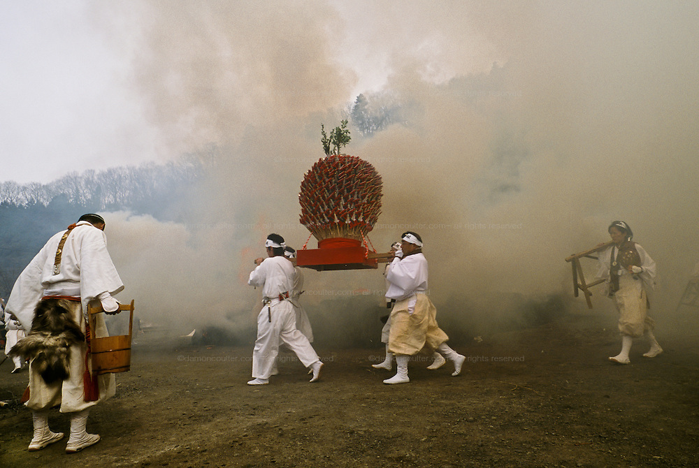 Yamabushi or Mountain priests in carry a mikoshi of arrows through the smoke of a large bonfire before walk across hot coals during the Hi Watari fire walking festival in Takao san Guchi, near Tokyo, Japan. Sunday March 11th 2007