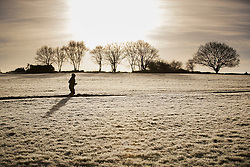 © Licensed to London News Pictures. 03/01/2017. Epsom, UK. Joggers exercise on a frost covered Epsom Downs. Parts of the UK are experiencing temperatures as low as -5 degrees centigrade. Photo credit: Peter Macdiarmid/LNP