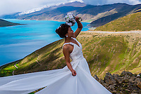 A Chinese bride posing for a wedding photograph with 45 mile long Yamdrok Tso Lake (14,570 feet) in the background. It is the largest lake and one of the three sacred lakes in Tibet (Xizang), China.