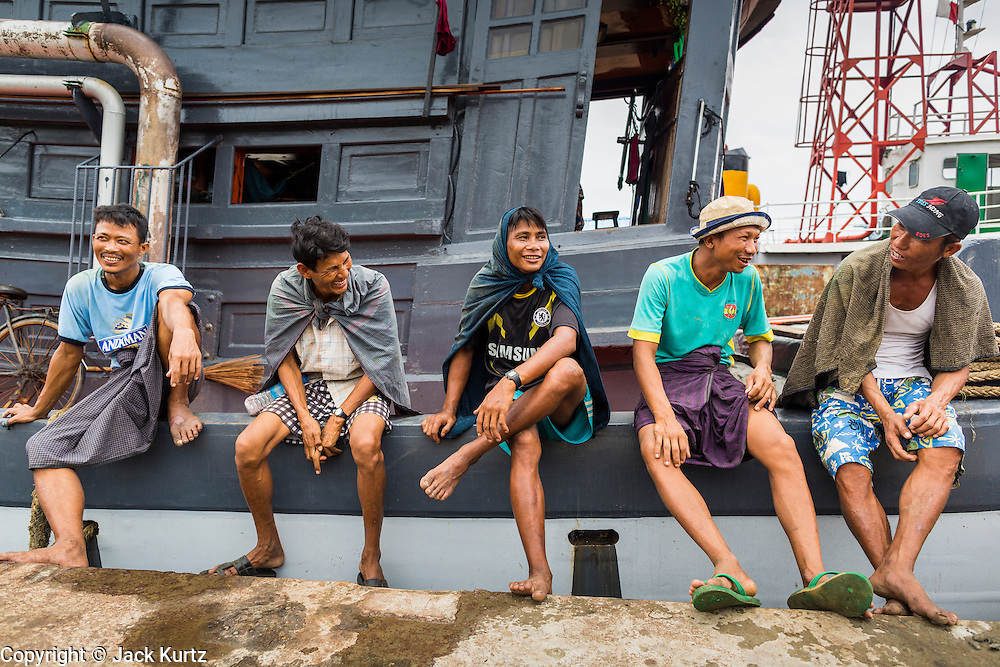"""10 JUNE 2014 - YANGON, MYANMAR:   Stevedores wait to go to work offloading 110 pound (50 kilo) sacks of fish meal from a river freighter on the banana jetty. The """"banana jetty"""" is on the Yangon River north of central Yangon on Strand Road. Bananas, coconuts and other fruit are brought in here from upcountry, sold and reshipped to other parts of Myanmar (Burma). All of the labor here is done by hand. Porters carry the produce to the jetty and porters load the boats before they steam upriver.   PHOTO BY JACK KURTZ"""