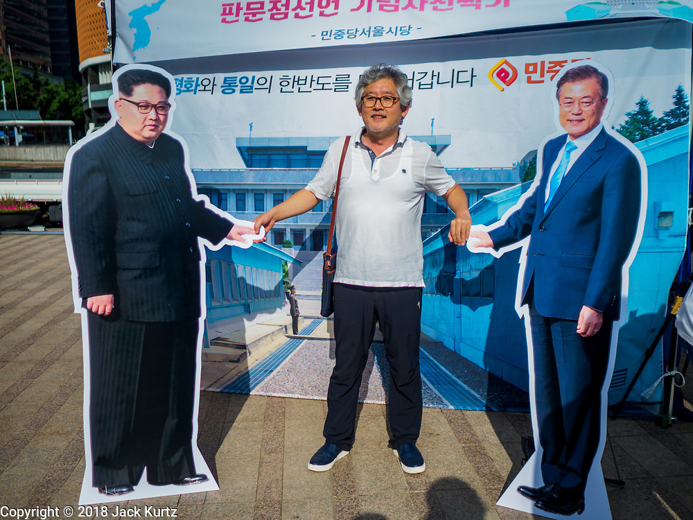 """15 JUNE 2018 - SEOUL, SOUTH KOREA: A man stands between cardboard cutouts of North Korean leader Kim Jong-un (left) and South Korean President Moon Jae-in during a rally to mark the anniversary of the signing of the June 15th North–South Joint Declaration between South Korea and North Korea. The Declaration was negotiated by late South Korean President Kim Dae-jung and North Korean leader Kim Jong-il and signed on 15 June 2000. It was a part of South Korea's """"Sunshine Policy,"""" which guides the South's relationship with North Korea. This year's observance of the anniversary was bolstered by the recent thawing in relations between North Korea and South Korea and the US.     PHOTO BY JACK KURTZ"""