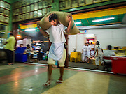 23 SEPTEMBER 2014 - BANGKOK, THAILAND: A man dressed in white for the religious observance of the Vegetarian Festival carries a sack of rice into a storeroom  at the Chit Sia Ma Chinese shrine in Bangkok. The Vegetarian Festival is celebrated throughout Thailand. It is the Thai version of the The Nine Emperor Gods Festival, a nine-day Taoist celebration beginning on the eve of 9th lunar month of the Chinese calendar. During a period of nine days, those who are participating in the festival dress all in white and abstain from eating meat, poultry, seafood, and dairy products. Vendors and proprietors of restaurants indicate that vegetarian food is for sale by putting a yellow flag out with Thai characters for meatless written on it in red.    PHOTO BY JACK KURTZ