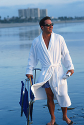 Man in sunglasses and white robe carrying a beach chair on the shore in Santa Monica, CA