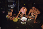 DAYAK EATING MALAYSIA. Sarawak, Borneo, South East Asia. Eating food from the forest. Tropical rainforest and one of the world's richest, oldest eco-systems, flora and fauna, under threat from development, logging and deforestation. Home to indigenous Dayak native tribal peoples, farming by slash and burn cultivation, fishing and hunting wild boar. Home to the Penan, traditional nomadic hunter-gatherers, of whom only one thousand survive, eating roots, and hunting wild animals with blowpipes. Animists, Christians, they still practice traditional medicine from herbs and plants. Native people have mounted protests and blockades against logging concessions, many have been arrested and imprisoned.
