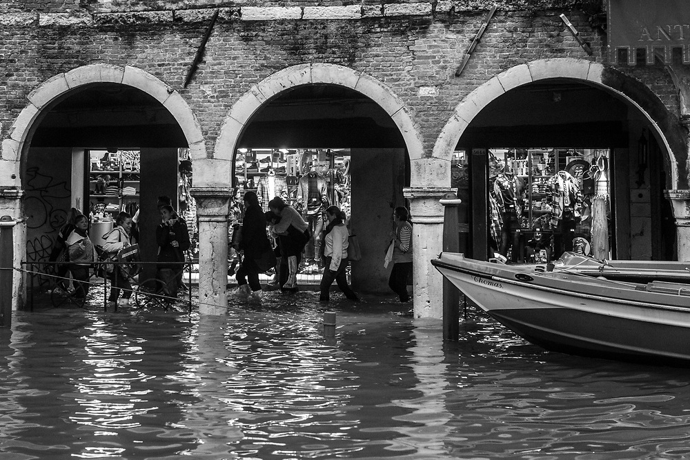 Venice, Italy. 29 October, 2018. People walk through a flooded portio during the high tide on October 29, 2018, in Venice, Italy. This is a selection of pictures of different areas of Venice that the press has not covered, were resident live and every year they have to struggle with the high tide. Due to the exceptional level of the 'acqua alta' or 'High Tide' that reached 156 cm today, Venetian schools and hospitals were closed by the authorities, and citizens were advised against leaving their homes. This level of High Tide has been reached in 1979. © Simone Padovani / Awakening / Alamy Live News