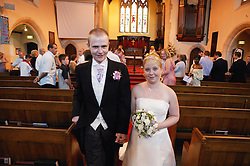 Bride and groom leaving church following marriage ceremony,