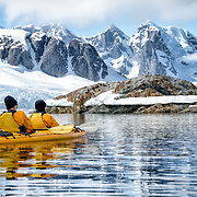 Kayakers paddle along in glassy conditions  next to scenic mountains on the shoreline near Petermann Island on the western side of the Antarctic Peninsula.
