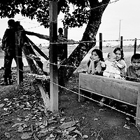 A group of children play 'school' near a checkpoint anned by Government soldiers, Puerto Asis, Putumayo.<br />