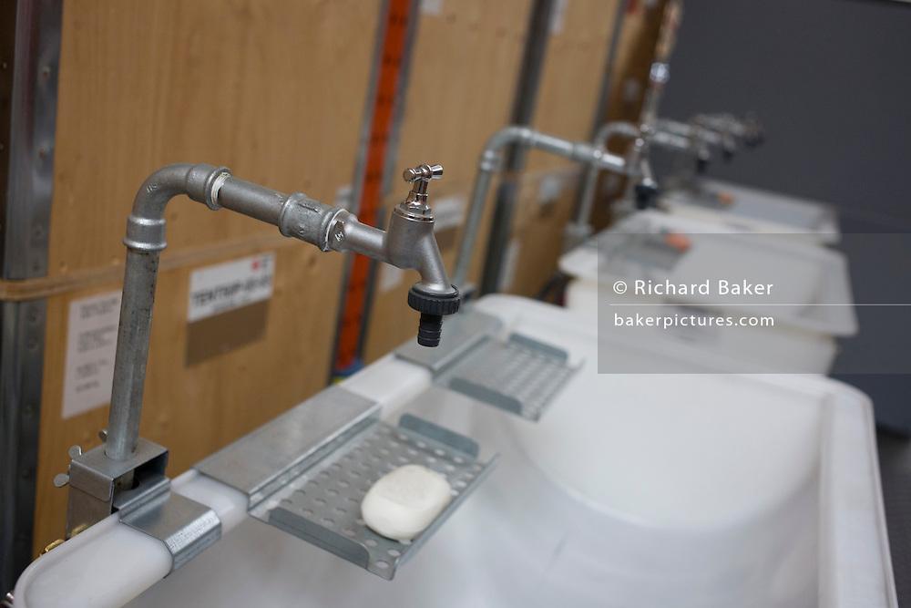 Sanitation wash sinks in emergency supplies warehouse, Deutsches Rotes Kreuz (DRK - German Red Cross) at their logistics centre at Berlin-Schönefeld airport.