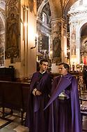 "Two Nazarenos from ""la quinta angustia"" brotherhood inside their parish church of Santa Maria Magdalena in Seville. Andalusia, Spain."