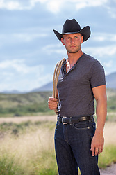 rugged cowboy with a lasso outdoors on a ranch
