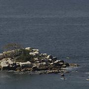 Kayakers near rock island. Acapulco, Guerrero, Mexico.
