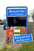 Nederland, berg en Dal, 23-03-2016 Vanwege de gemeentelijke herindeling is de samenvoeging van de gemeenten Millingen aan de Rijn, Ubbergen en Groesbeek een feit en worden de komborden van de dorpskernen vervangen. Sinds 1 januari 2016 heet de nieuwe gemeente Berg en Dal. Het oude bord , wordt vervangen door het nieuwe. FOTO: FLIP FRANSSEN/ HH