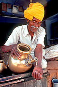 INDIA, RAJASTHAN, MARKETS,  a water vendor pouring water from a  brass urn in the market in Jaipur