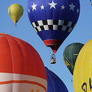 Rhett Heartsill, USA, (ninety-nine) and other hot air balloons in the skies around rural Michigan near Battle Creek as they reach a target area during competition in the 20th FAI World Hot Air Ballooning Championships. Battle Creek, Michigan, USA. 22nd August 2012. Photo Tim Clayton