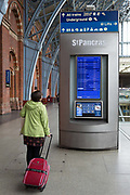 As the UK government urged that all Britons should avoid non-essential travel abroad in order to combat the Coronavirus pandemic in Britain, a lady rail passenger looks at departures information at an unusually quiet  concourse  St. Pancras rail station, the London terminus for Eurostar services to mainland Europe, on 17th March 2020, in London, England.
