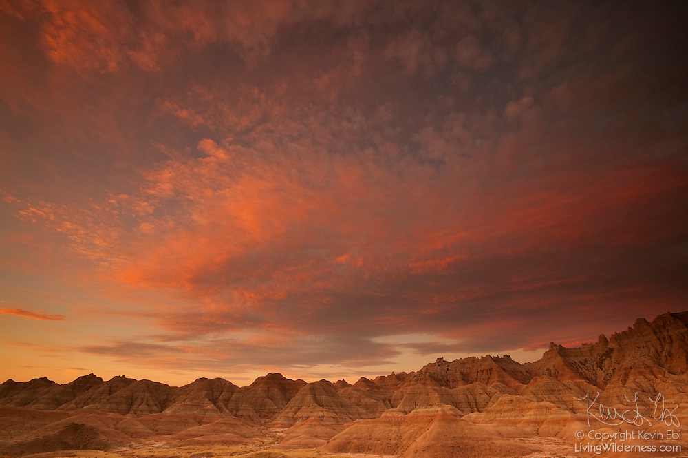 A fiery fall sunrise lights up the sky above countless peaks that make up the Badlands in Badlands National Park, South Dakota.