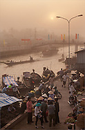 The sun has just come up in Soc Trang and many merchants and traders are already busy. The Mekong waterways support much trade of produce, fish and other good products. The flags on the bridge were hung to celebrate Tet, the Lunar New Year. Robert Dodge, a Washington DC photographer and writer, has been working on his Vietnam 40 Years Later project since 2005. The project has taken him throughout Vietnam, including Hanoi, Ho Chi Minh City (Saigon), Nha Trang, Mue Nie, Phan Thiet, the Mekong, Sapa, Ninh Binh and the Perfume Pagoda. His images capture scenes and people from women in conical hats planting rice along the Red River in the north to men and women working in the floating markets on the Mekong River and its tributaries. Robert's project also captures the traditions of ancient Asia in the rural markets, Buddhist Monasteries and the celebrations around Tet, the Lunar New Year. Also to be found are images of the emerging modern Vietnam, such as young people eating and drinking and embracing the fashions and music of the west. His book. Vietnam 40 Years Later, was published March 2014 by Damiani Editore of Italy.