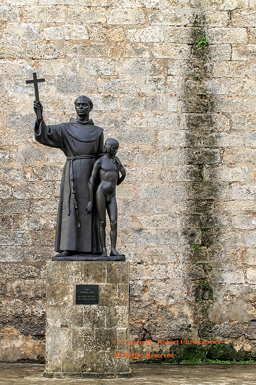 Catholic Stain:  In this statue, Fray Junipero Serra stands aside Juaneño (an Indian boy) and is found next to a large dark stain on the Basilica Menor de San Francisco de Asis; symbolic of the current sex scandal that taints the Catholic Church, in the plaza de San Francisco, Havana Cuba.