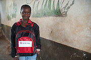 Mariana, 12, poses for a photograph in the school yard. <br /> Save the Children distributed education kits to students at Groupe Scolaire Quartier Lycée in Man, western Côte d'Ivoire. Children received a backpack with school supplies such as pens, pencils, sharpeners, notebooks, rulers, a pair of compasses and a portable chalkboard.