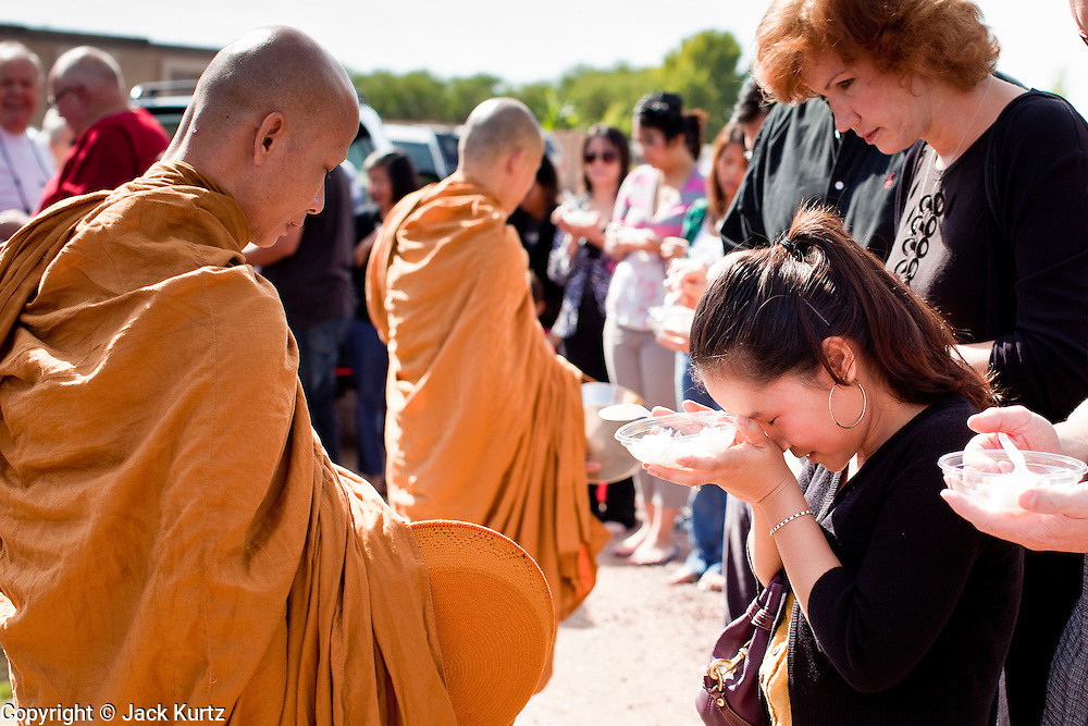 """24 OCTOBER 2010 - CHANDLER, AZ: A Thai woman bows after presenting Ajahn MAHA AMPORN with rice during the """"tak bat"""" or donation of rice to the monks, an important part of Buddhist merit making, during the Ok Phansa services to mark the end of Buddhist Lent at Wat Pa, in Chandler, AZ, Sunday October 24. Buddhist Lent is a time devoted to study and meditation. Buddhist monks remain within the temple grounds and do not venture out for a period of three months starting from the first day of the waning moon of the eighth lunar month (in July) to the fifteenth day of the waxing moon of the eleventh lunar month (in October). Ok Phansa Day marks the end of the Buddhist lent and falls on the full moon of the eleventh lunar month, this year Oct 23. Wat Pa, a Thai Theravada Buddhist temple, celebrated Ok Phansa Day on October 24.    Photo by Jack Kurtz"""