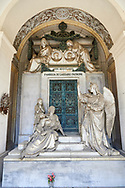 Picture and image of the stone sculpture of a mouyring widow and two children sitting by the doors of the tomb with an angel. The Patrone tomb sculpted by S Varni 1976. Section D, no 23, The monumental tombs of the Staglieno Monumental Cemetery, Genoa, Italy .<br /> <br /> Visit our ITALY PHOTO COLLECTION for more   photos of Italy to download or buy as prints https://funkystock.photoshelter.com/gallery-collection/2b-Pictures-Images-of-Italy-Photos-of-Italian-Historic-Landmark-Sites/C0000qxA2zGFjd_k<br /> If you prefer to buy from our ALAMY PHOTO LIBRARY  Collection visit : https://www.alamy.com/portfolio/paul-williams-funkystock/camposanto-di-staglieno-cemetery-genoa.html