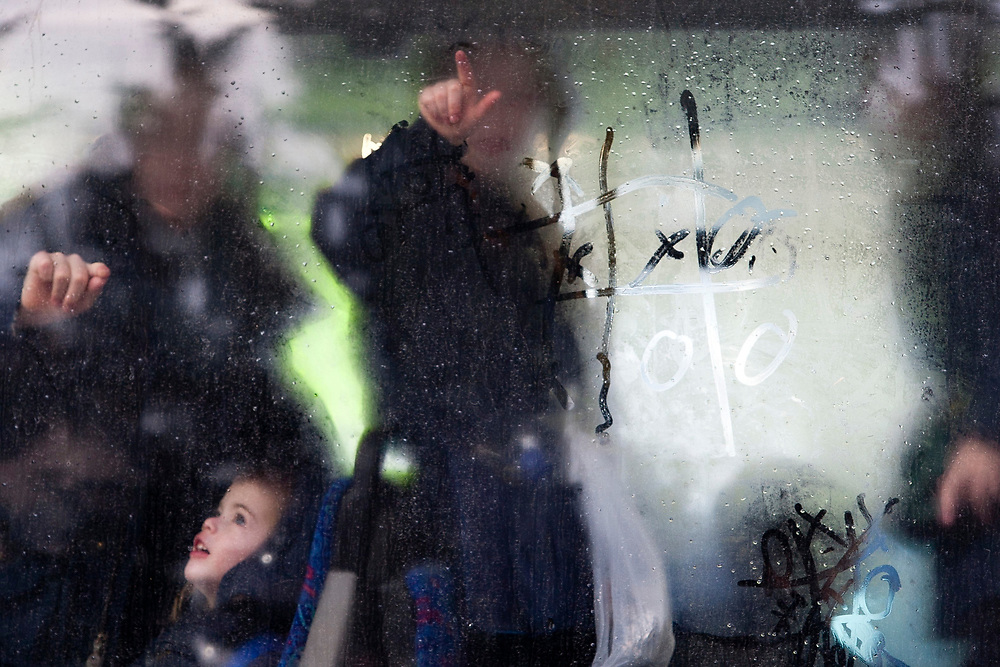 Ultra-Orthodox Jewish children play a game of Tic-Tac-Toe on the foggy window of a bus during a cold winter day in Jerusalem on January 9, 2011.